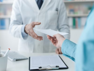 Customer handing a medical prescription to the pharmacist, treatment and healthcare concept